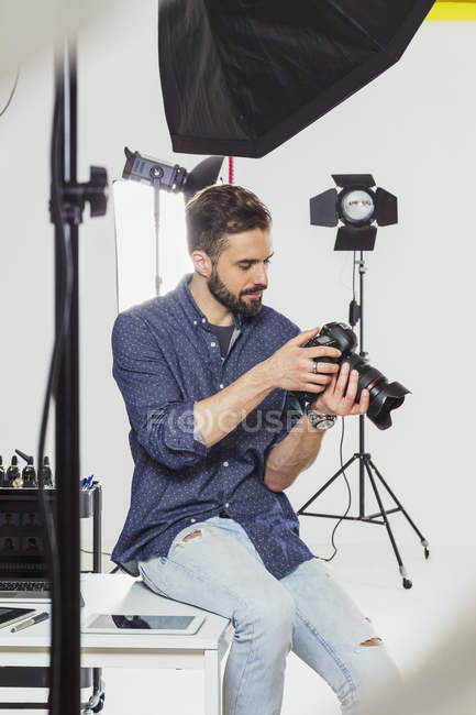 Man photographer reviewing photography shoot on digital SLR in photography studio — Foto stock