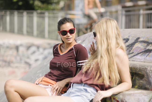 Two female skateboarding friends chatting in skatepark — Stock Photo
