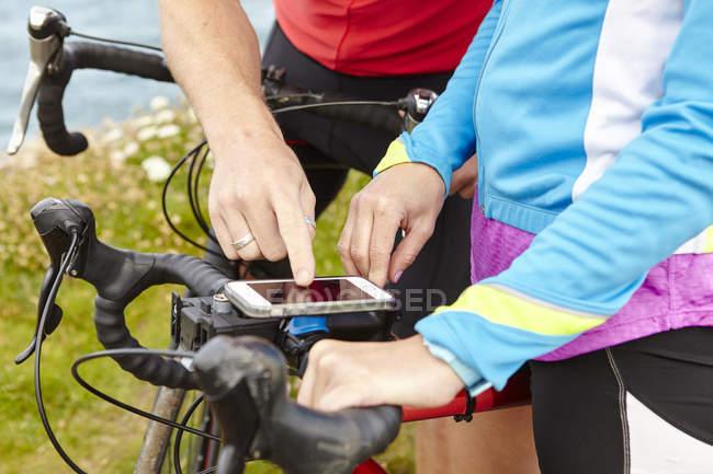 Велосипедисти, зупиняючись, щоб використовувати Gps мобільного телефону — стокове фото