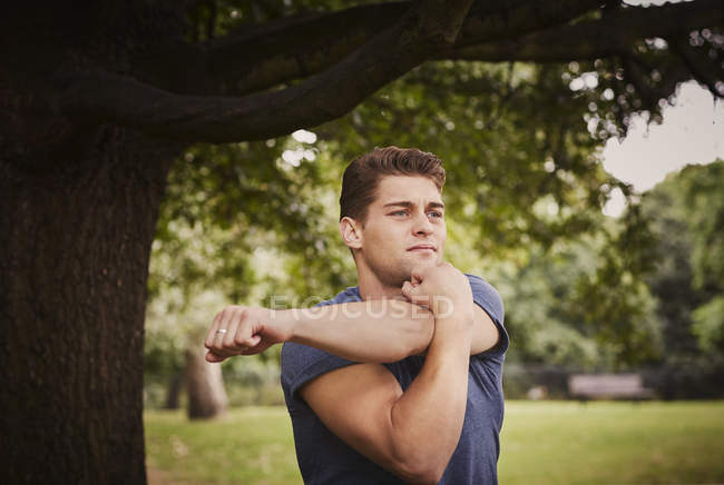 Young man training, warming up in park — Stock Photo