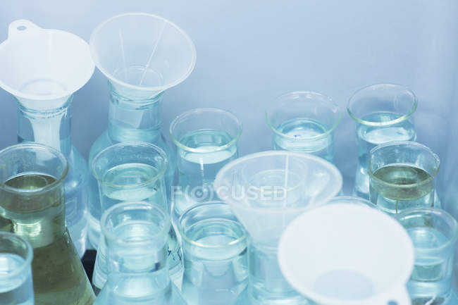 Funnels and beakers filled with liquid — Stock Photo