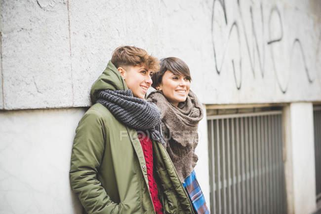Dos hermanas apoyadas en la pared, mirando hacia otro lado - foto de stock