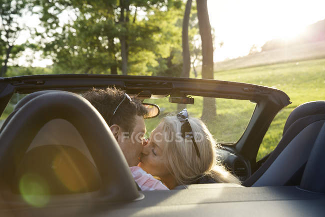Mature couple kissing in convertible car — Stock Photo