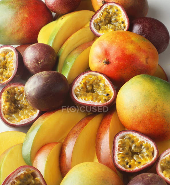 Pile of mangoes and passion fruit, sliced and whole — Stock Photo