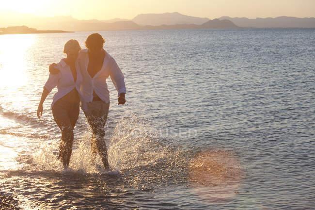 Coppia passeggiando in acqua di mare con spruzzi, tramonto sullo sfondo — Foto stock