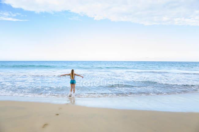 Veduta posteriore di una giovane donna che corre in mare, Repubblica Dominicana, Caraibi — Foto stock