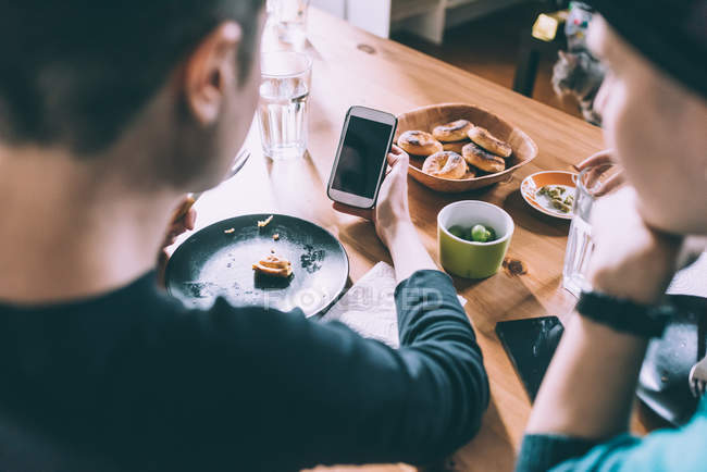 Over shoulder view of two young female friends reading smartphone texts at kitchen table — Stock Photo