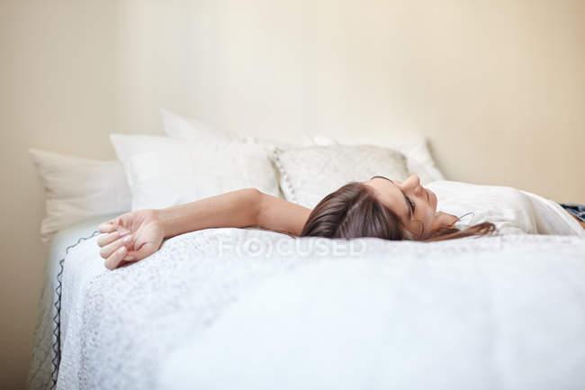 Superfície vista nível da jovem mulher deitada na cama — Fotografia de Stock