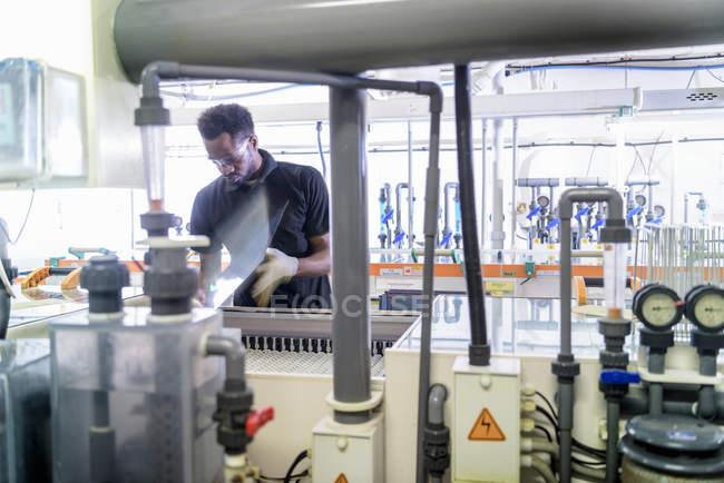 Ouvrier utilisant la machine de traitement de circuit dans l'usine d'électronique — Photo de stock
