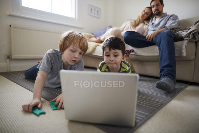 Brothers playing laptop game on room rug, parents on sofa — Stock Photo