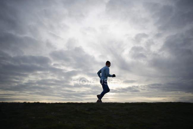 Niedrigen Winkel voller Länge Seitenansicht des Läufers vor dramatischen Himmel — Stockfoto