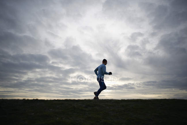 Low angle full length side view of runner against dramatic sky — Stock Photo