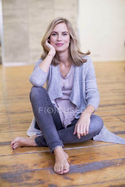Porträt von Mitte Erwachsene Frau, sitzt am Boden, ruht auf Knie, Ellenbogen lächelnd — Stockfoto