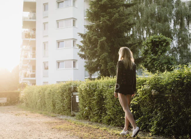 Mujer joven al aire libre, caminando por la calle, vista trasera - foto de stock