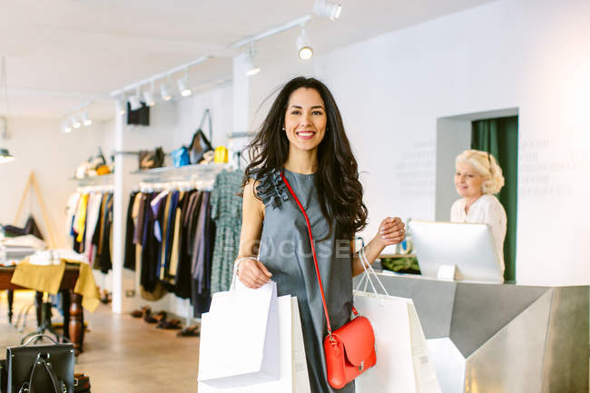 Woman leaving clothes shop carrying shopping bags smiling — Stock Photo