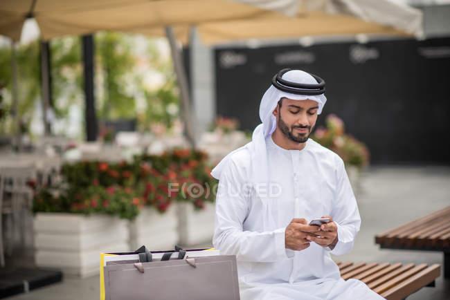 Shopper mâle portaient des vêtements traditionnels du Moyen-Orient, assis sur un banc de lecture de texte, Dubaï, Émirats Arabes Unis smartphone — Photo de stock