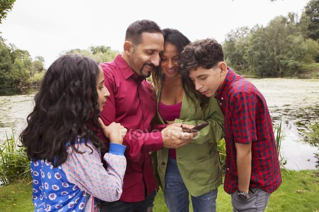 Famille debout à l'extérieur, regardant smartphone, souriant — Photo de stock