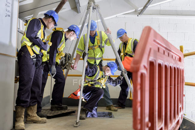 Apprentice builders learning how to use hoist in training facility — Stock Photo