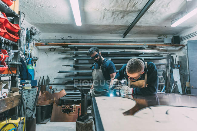 Metalworker cutting copper with welding torch in forge workshop — Stock Photo
