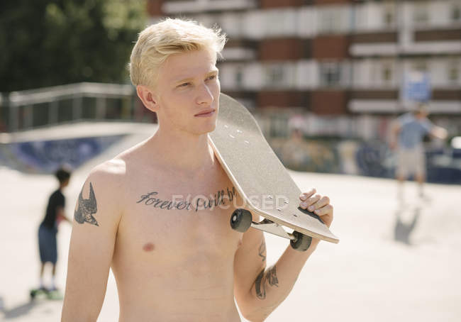 Tattooed young man carrying skateboard on shoulder in skatepark — Stock Photo