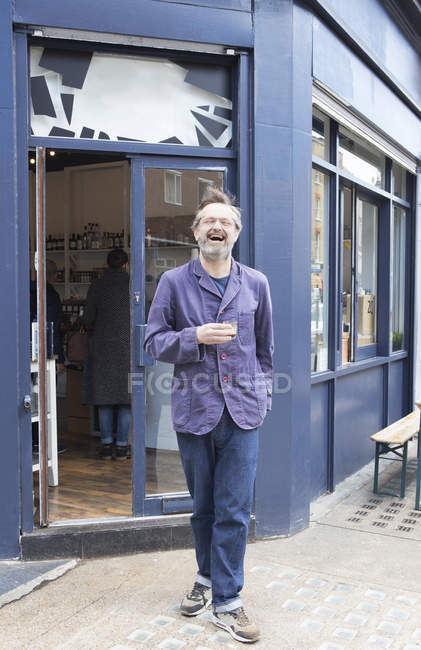 Portrait of male cafe owner laughing and drinking espresso on street — стокове фото