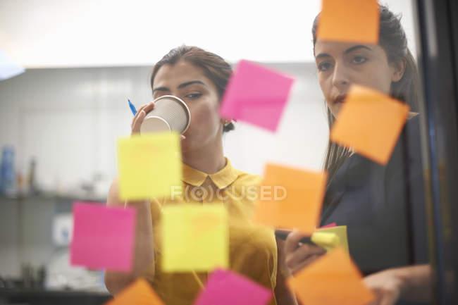 Два бізнесжінки п'ють каву і дивилися на липких нот на офісні скляні стіни — стокове фото