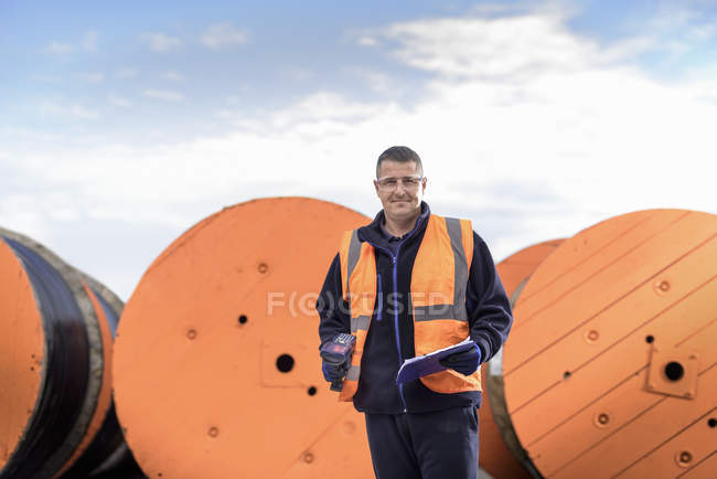 Worker inspecting electrical cable reels at cable storage facility, portrait — Stock Photo