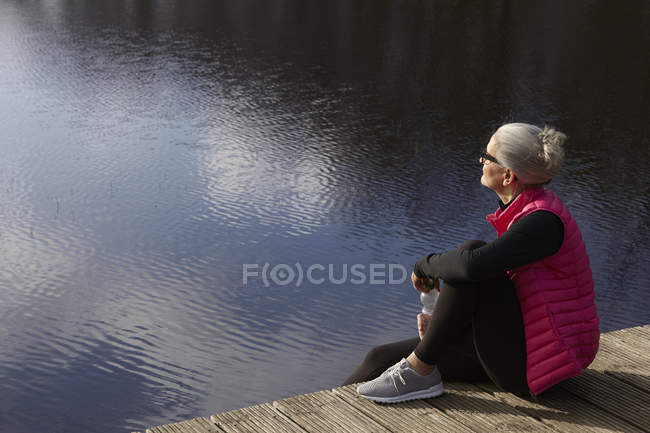 Side view of woman sitting on wooden pier looking away — Stock Photo