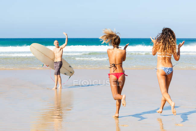 Male surfer waving to female friends on beach, El Cotillo, Fuerteventura, Spain — Stock Photo