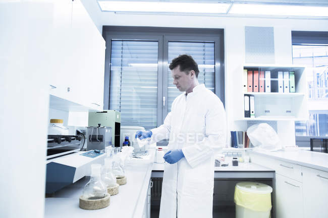 Scientist examining sample inside beaker in laboratory — Stock Photo
