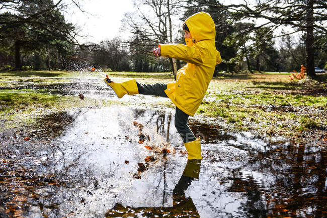 Boy in yellow anorak splashing in park puddle — Stock Photo