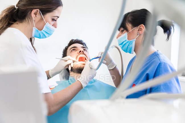 Dentista femminile e infermiera dentale utilizzando trapano dentale sul paziente maschile — Foto stock