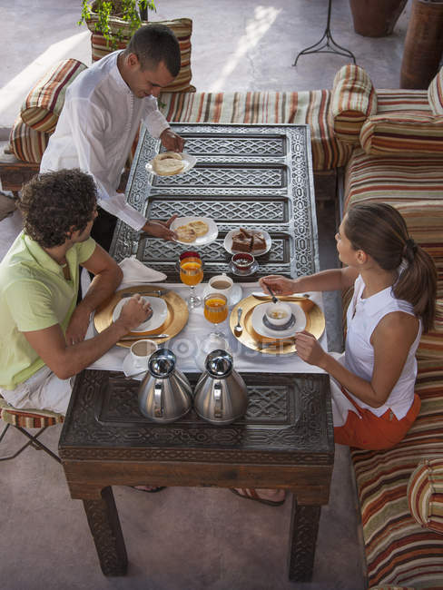 Waiter serving young couple breakfast, Marrakesh, Morocco — Stock Photo