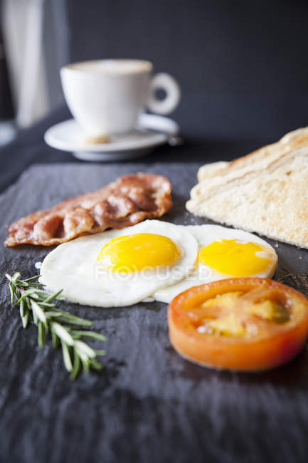 Toast with bacon, fried eggs and tomato on slate — Stock Photo