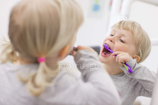 Spiegelbild der blonde Mädchen mit Trauben, Mund offen Zähneputzen — Stockfoto
