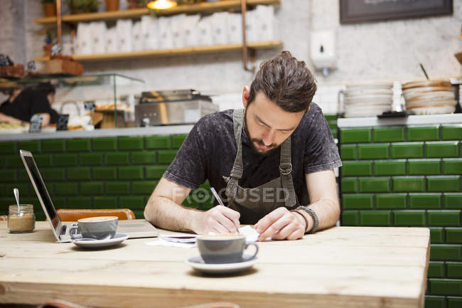 Young male cafe owner doing paperwork at table — Stock Photo