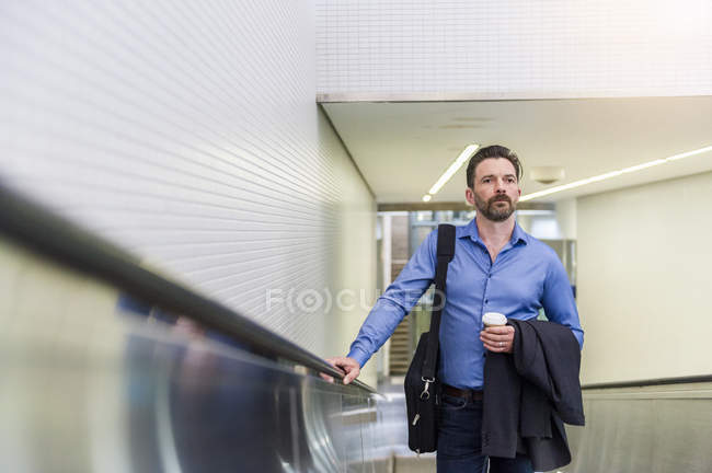 Mature businessman with takeaway coffee moving up escalator — Stock Photo
