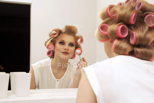 Young woman in curlers putting on make-up — Stock Photo