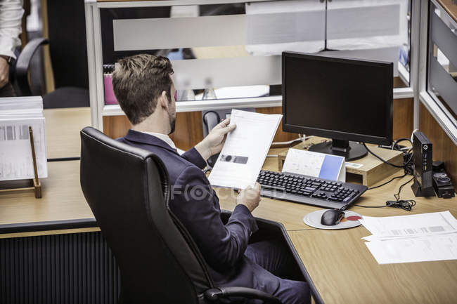 Businessman reading paperwork at office desk — Stock Photo
