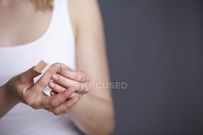 Cropped close up shot of young woman applying adhesive plaster to her own finger — Stock Photo