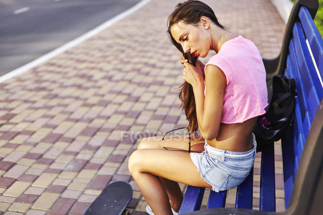 Young woman sitting on bench, fixing hair, skateboard on floor beside her — Stock Photo