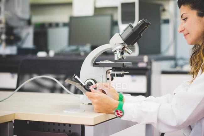 Wissenschaftlerin mit digitalem Tablet und optischem Mikroskop — Stockfoto