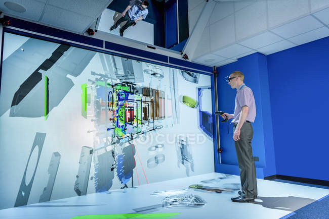Engineer looking at component parts of machine in 3D in virtual reality suite — Stock Photo