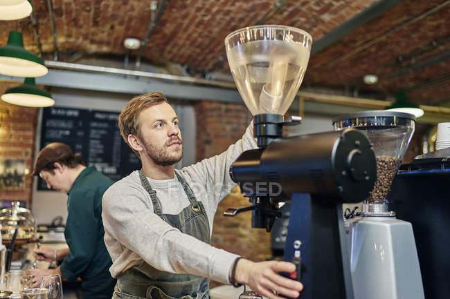 Мужчина-бариста с помощью кофеварки на кухне кафе счетчик — стоковое фото