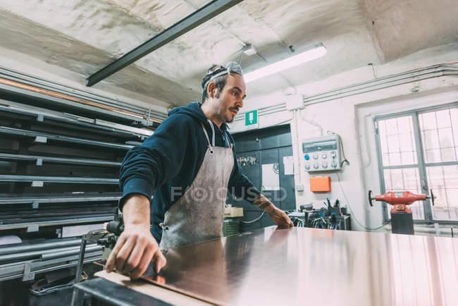 Metallarbeiter heben Blech Kupfer in Schmiedewerkstatt — Stockfoto