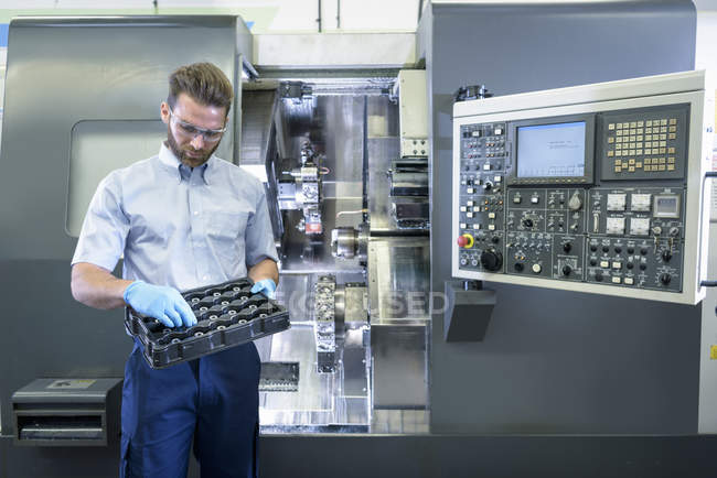 Engineer with CNC lathe in automotive parts factory — Stock Photo