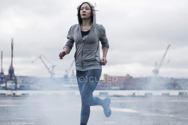 Jeune coureur féminin en cours d'exécution sur les quais orageux — Photo de stock