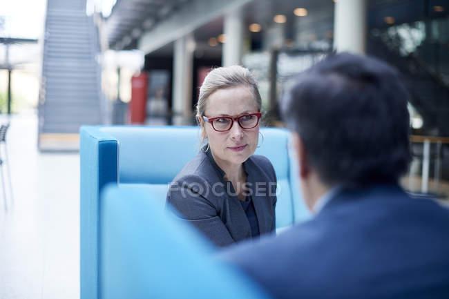 За плече зору ділової жінки і людини на зустрічі в кабінеті атріуму — стокове фото