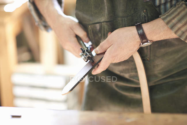 Male worker in leather workshop, punching holes in leather belt, mid section, close-up — Stock Photo