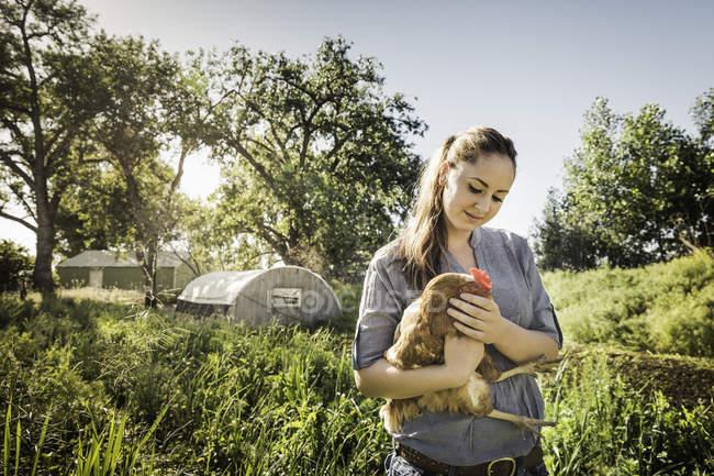 Mujer sosteniendo pollo en tierra de cultivo sonriendo - foto de stock